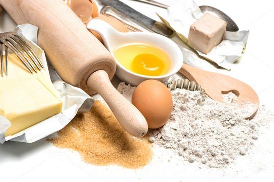 baking ingredients eggs, flour, sugar, butter, yeast. food background